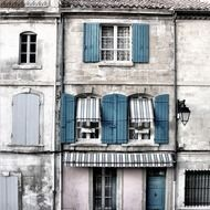 windows with blue shutters on grey facade of old house, france, provence
