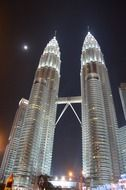 Petronas Towers is a complex of buildings in Kuala Lumpur against the night sky