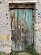 weathered wooden door in stone facade