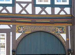 shield with angls and golden lettering at top of gates in aged truss house