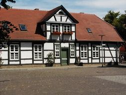 truss building with windows on red tile roof, germany