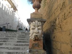 ancient fountain with stone carved face at stairs outdoor, spain, majorca