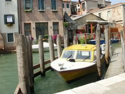 motor boats parked on channel at old buildings, italy, venice