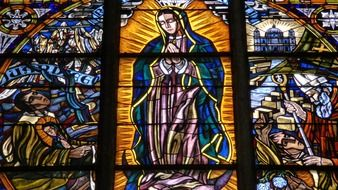praying virgin mary drawing on stained glass window of church