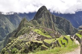 ancient ruins of machu picchu on mountain under clouds, peru, andes