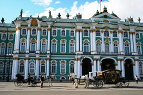 horse-drawn carriages on square at winter palace, russia, st petersburg