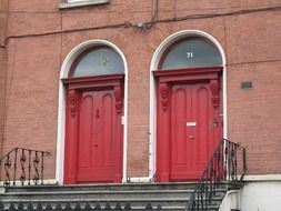 two old arched red doors on porch, ireland, dublin