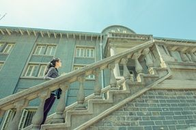 young asian girl stands on stairs at facade of old building, china, nanjing