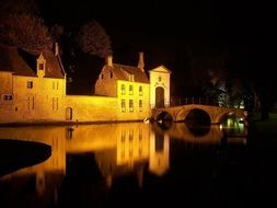 old town mirroring on water at night, belgium, bruges