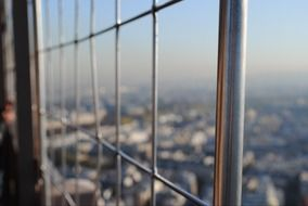 out of focus view of city through metall grid