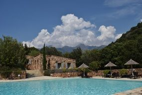 Swimming pool clouds mountains corsica view
