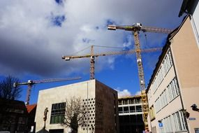 Construction cranes against a background of thunderclouds