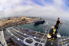 man working on mast in view of uss carl vinson Nimitz-class supercarrier at harbour, usa, california, san diego