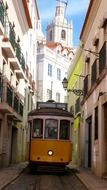 yellow tram in alley of old town, portugal, lisbon