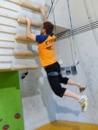 young man hanging on climbing wall