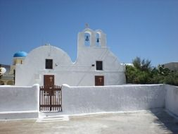 White orthodox church behind white stone fence, greece, santorini