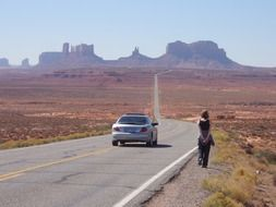 car and walking woman on road to monument valley rock formations, usa, utah, arizona