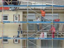 workers on scaffolding at house under construction