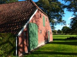 red brick farm building with tile roof at summer