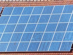 blue solar cells on red tile roof