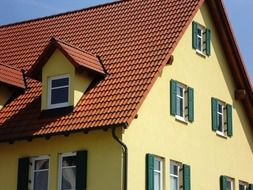 house with yellow facade and red tile roof