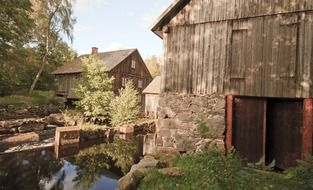 old farm buildings at stream, sweden