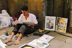 young artist painting at ancient angkor wat temple, cambodia, siem reap
