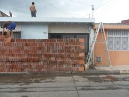 men working with red brick at building