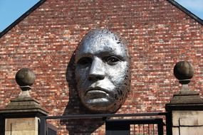 face, sculpture on brick wall, uk, england, lincoln, drill hall