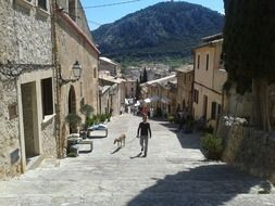 man with dog walking up scenic street, spain, majorca