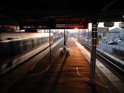 train passing platform of nishi-gifu railway station at sunset, japan, gifu