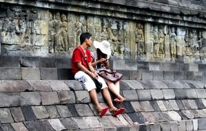 young asian boy and girl sitting at ancient buddhist temple, indonesia, java