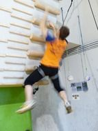 young man on climbing wall, strength training