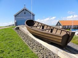 wooden boat on hill at blue building, netherlands