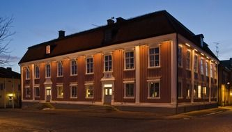 illuminated two-storey corner building at night, sweden