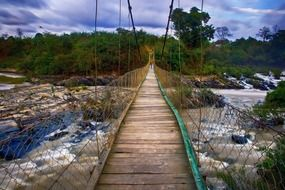 long pedestrian suspension bridge across foamy waterflow