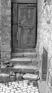 closed old wooden door at stone steps