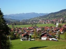 picturesque village in valley at green mountains, germany, allgäu, bad oberdorf