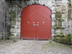 red metal sheet gate in aged grey stone wall, denmark