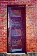 partly open old wooden door in brick wall