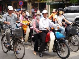 people riding motorcycles and bicycles on street in city, vietnam, hanoi