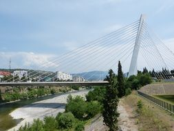 suspension bridge across foamy river, montenegro, podgorica