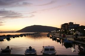 boats at pier in coastal town at dusk, greece, lefkas, lefkada