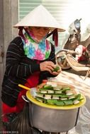 vietnamese woman in cone hat cooking traditional meal, vietnam, ho chi minh city