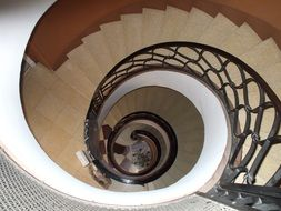 stone spiral staircase with metal railing indoor
