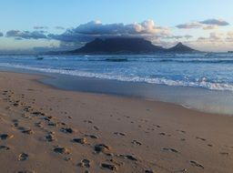 footprints on beach in view of table mountain under clouds, south africa, cape town