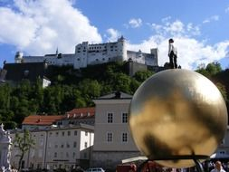 person at top of golden sphere in view of city and hohensalzburg fortress, austria, salzburg