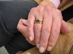 folded hands of old woman with gold ring on finger
