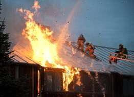 firefighters at work on roof of burning building, usa, alasla