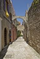 old alley with arches connecting houses, greece, rhodes